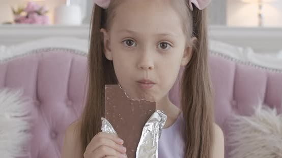 Thumbnail for Close-up of Happy Little Girl Chewing Chocolate at Home, Satisfied Face of Pretty Brunette Caucasian