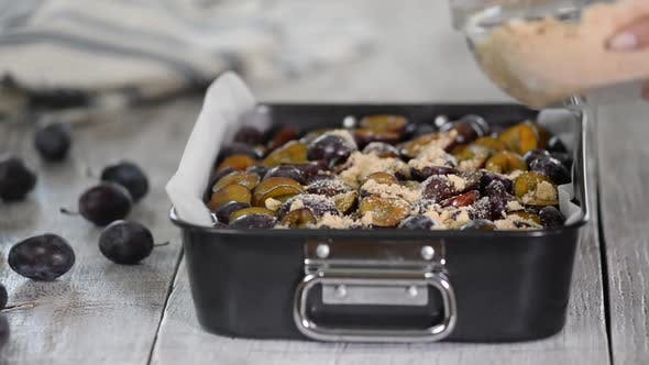 Thumbnail for The process of making a fruit pie. Woman hands sprinkle crumble on the plum cake.