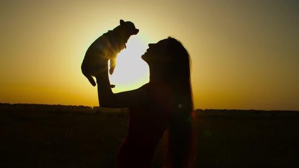 Caring Female Dog Owner Holding Lapdog at Sunset