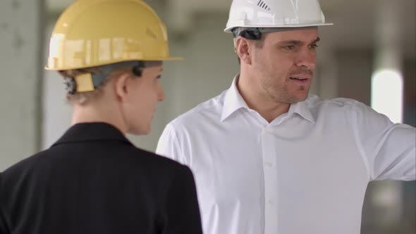 Thumbnail for Happy Smiling Businessman and Businesswoman Talking While Working at Constructions Site