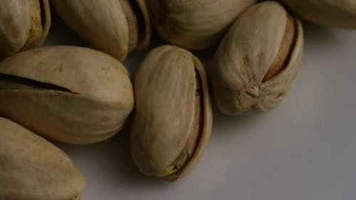 Cinematic, rotating shot of pistachios on a white surface - PISTACHIOS 009