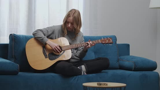 A Teenage Girl in Home Clothes Plays a New Melody Melody on a Classical Guitar Sits