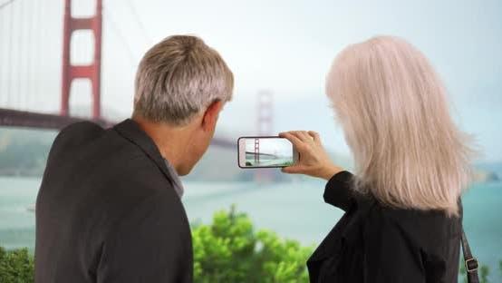 Thumbnail for Senior couple taking photos of landmarks with smartphone