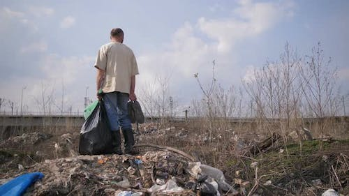 Man Standing on Garbage Hill at Landfill Site