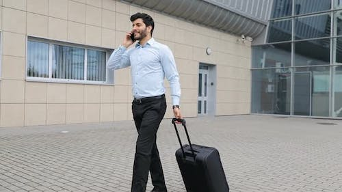 çBusiness Trip. Handsome Man With Phone And Suitcase At Airport