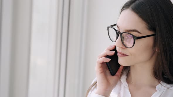 Pretty Woman in Glasses Is Making a Call Near the Window and Smiling