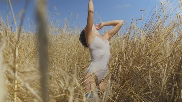Thumbnail for Chic Woman with Short Hair Wearing Bodysuit Relaxing on the Wheat Field. Girl Enjoys Nature Looking