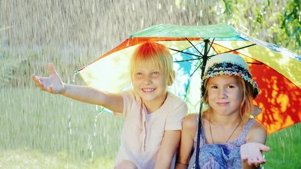 Thumbnail for Two Cheerful Girlfriends 5 Years Hiding From the Rain Under an Umbrella Rainbow Colors. Happy