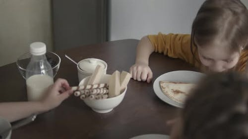 Children in Pajamas Have Breakfast at Home