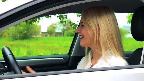 Young Attractive Blond Woman Sits in the Car and Rajoices