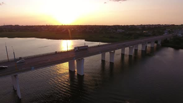 Cover Image for Aerial Shot of a Big Bridge with a Riding Semi-trailer at Golden Sunset in Summer