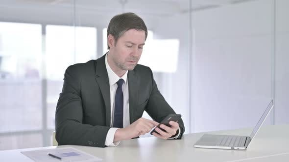 Thumbnail for Cheerful Middle Aged Businessman Using Smartphone in Office