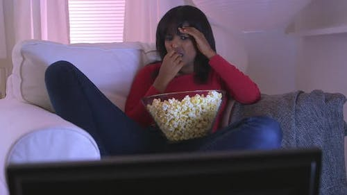 Black girl watching scary movie at home