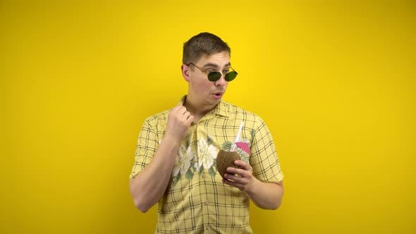 Thumbnail for The Man in Sunglasses and a Hawaiian Shirt Is Hot and Drinking Coconut Pina Colada. Shooting in the