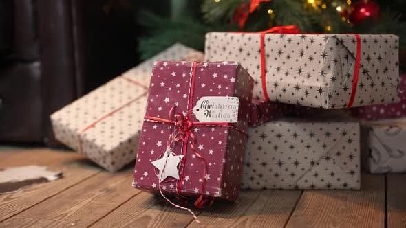 Belle boîte cadeau de Noël dans une pile de cadeaux reposent sur le plancher en bois sous l'arbre
