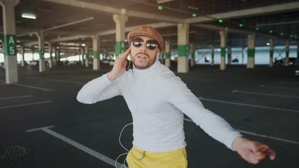 Handsome Happy Bearded Man Is Listening To Music in Smartphone Headphones and Dancing. Funny Dancer