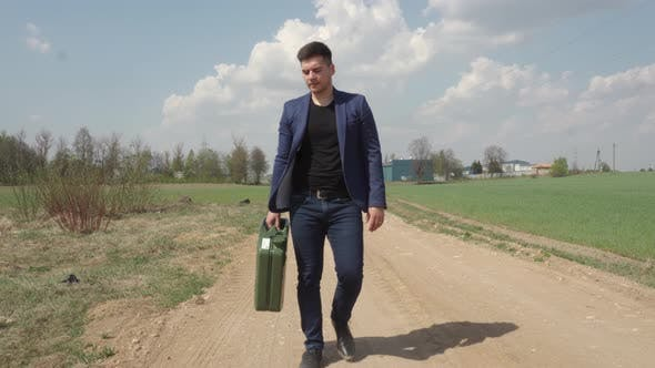 Thumbnail for Man Walks With Fuel Canister on a Dusty Road, his Car Run Out Of Fuel