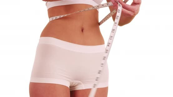 Thumbnail for Close up of slim young woman measuring waistline in studio with copy space