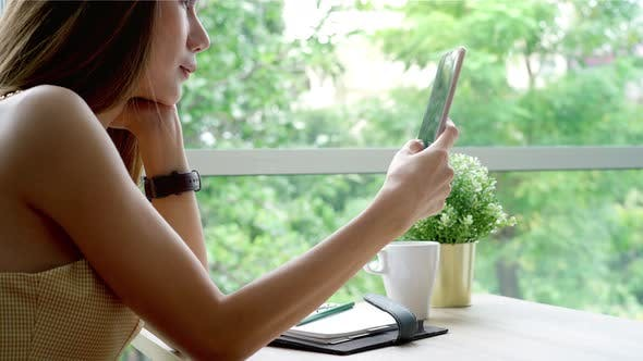 Thumbnail for Young Asian Woman Enjoying A Relaxing Moment in the Coffeeshop
