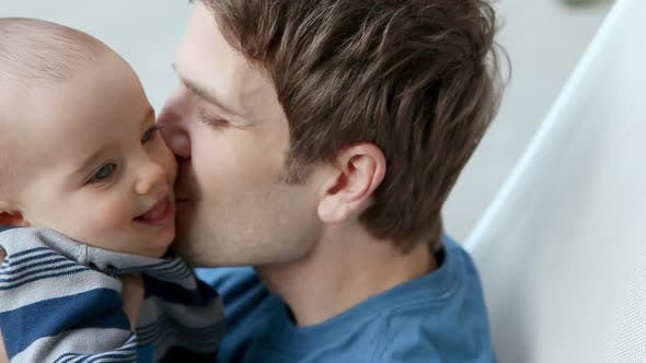 Thumbnail for Father kissing baby son on cheek