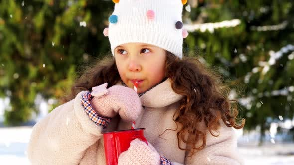 Kleines Mädchen trinken heißen Tee im Winter Park