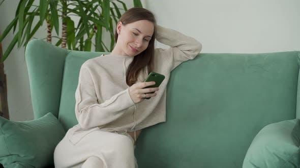 Lächelnde Frau entspannt sich, zu Hause auf der Couch zu sitzen, indem sie Textnachrichten auf dem Handy zum