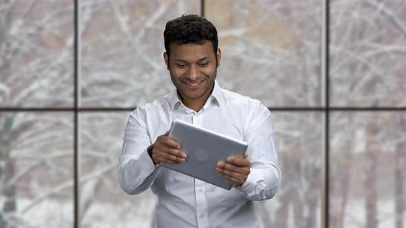 Cheerful Businessman Playing Game on Digital Tablet