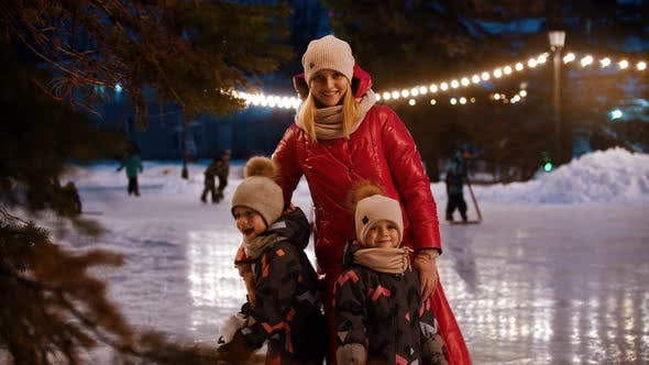Cover Image for A Family of Young Mother and Two Kids Standing on the Decorated Ice Rink and Waving with Their Hands
