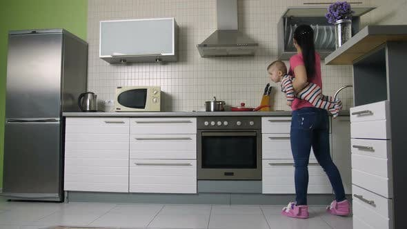 Thumbnail for Busy Mother Cooking in Kitchen Holding Baby Son