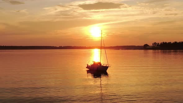 A Sailing Boat with Lowered Sails Stands Against the Backdrop of an Orange Beautiful Sunset