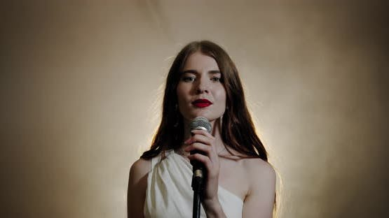 The Girl Singer Sings Into the Microphone and Completes the Song and Leaves, the Scene in Smoke