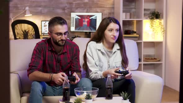 Joyful Young Couple Sitting on the Couple and Playing Video Games