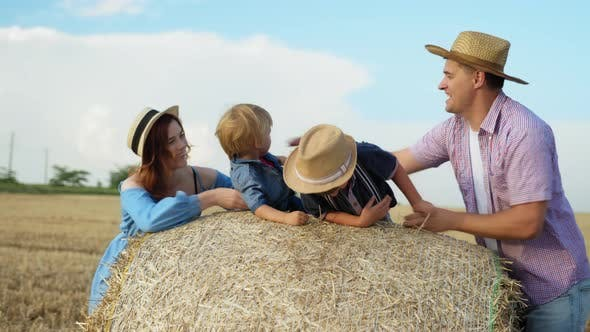 Family Relationships, Parents with Children on Haystack Enjoying Weekend in Countryside