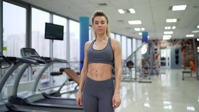 Gym woman standing by fitness machines inside in fitness center