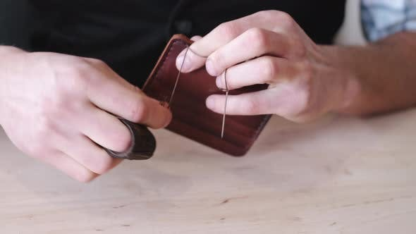 Thumbnail for The Tanner Is Stitching a Hand-made Leather Wallet