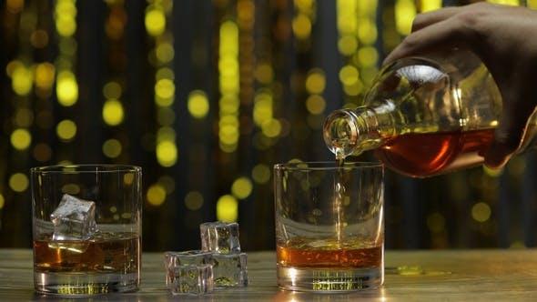 Gießen von Golden Whiskey, Cognac oder Brandy aus der Flasche in Glas mit Eiswürfeln. Glänzender Hintergrund
