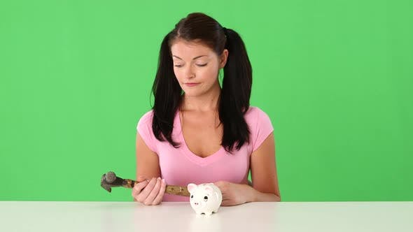 Thumbnail for Closeup portrait of young woman breaking piggy bank with hammer