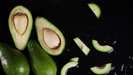 Falling Cut Fresh Avocados in the Water