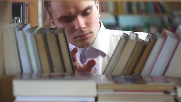 Thumbnail for Junge wählt ein Buch in der Bibliothek. Nahaufnahme. Zeitlupe