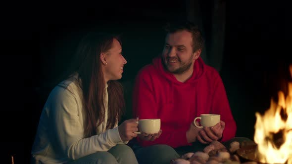 Thumbnail for Cute Millennial Couple Flirting While Drinking Tea By Fire on Patio at Night