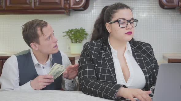 Young Confident Plump Woman Working with Laptop at the Table. A Timid Young Man Asking More Money