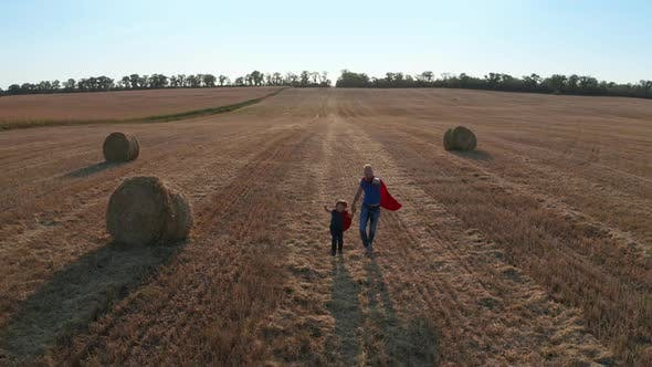 Thumbnail for Drone Shot of Father and Son Running Across Field