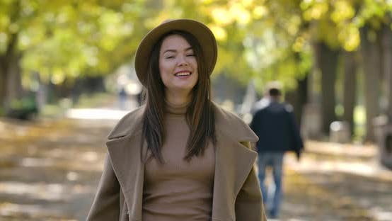 Thumbnail for Beautiful Caucasian Girl in Elegant Brown Hat and Coat Posing on the Background of Autumn Park