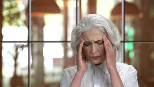 Old Lady with Headache Massaging Temples