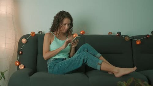 Young Woman is Using Smart Phone and Sits on Couch Leisurely in Living Room