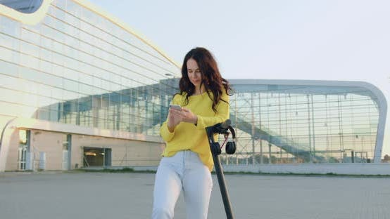 Girl Standing Near Personal E-scooter and Using Her Mobile