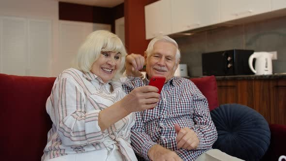 Thumbnail for Happy Smiling Senior Couple with Mobile Phone at Home. Resting on Sofa in Cozy Living Room