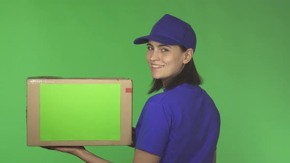 Thumbnail for Rear View Shot of a Delivery Woman with a Cardboard Box Smiling Over Her Shoulder