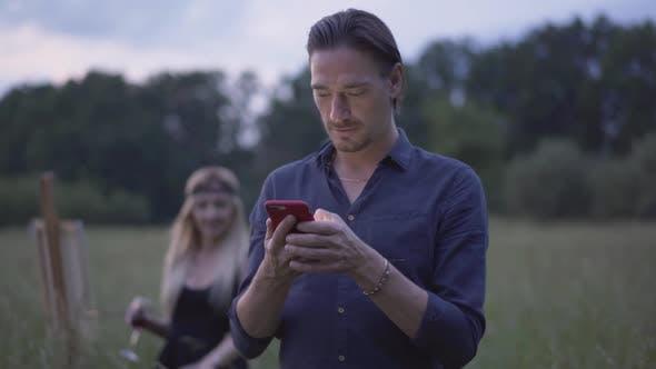Thumbnail for Porträt von Brünette kaukasischen Mann mit Smartphone als blond lächelnde Frau aus der
