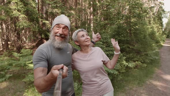 Thumbnail for Two Aged Sporty People Shooting Video in Woods